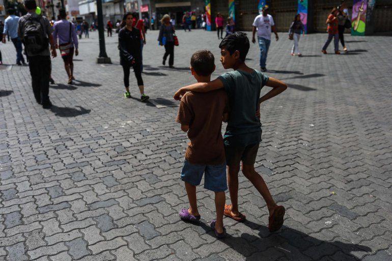 Dos niños solos caminan por el Bulevar de Sabana Grande, donde logran obtener algo de comer o algún dinero.