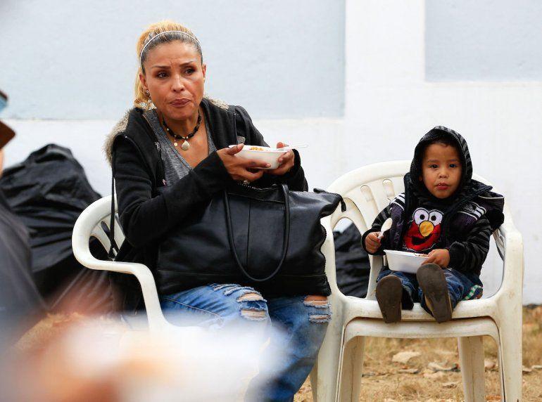 Un mujer alimenta a su hijo mientras espera seguir su camino fuera de Venezuela.