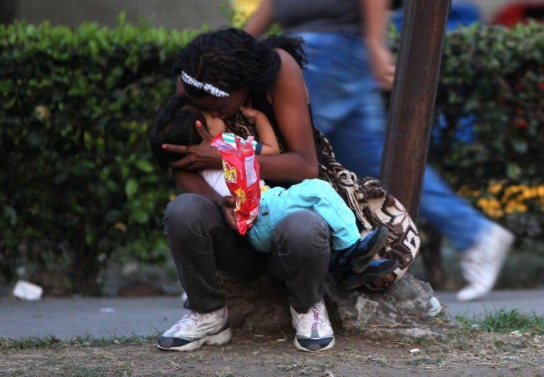 Una mujer venezolana abrazo a su hijo en una cera de Colombia mientras esperan para seguir su camino hacia Perú.
