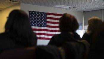 Varias personas esperan en una habitación frente a la bandera de los EEUU.