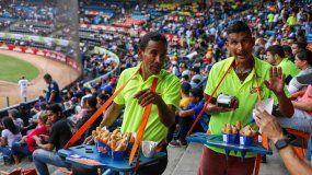 Vendedores ofrecen sus productos durante el juego inaugural de la temporada 2018-2019 en el estadio Universitario de Caracas, Venezuela, un alivio para muchos venezolanos dentro de la crisis que vive el país.