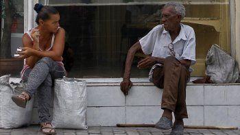 Una mujer conversa con un anciano en una calle de Santiago de Cuba, en el oriente de la isla.