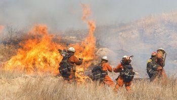 Los bomberos trabajan para extinguir un brote del incendio Woolsey en una colina en West Hills, California.