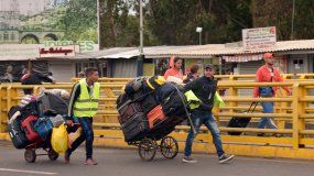 Un grupo demigrantesvenezolanos caminan con sus pertenencias en Rumichaca (Ecuador).