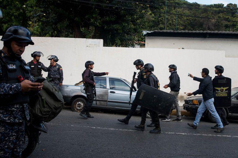 Miembros del Comando Nacional Antiextorsión y Secuestro CONAS retienen a un periodista este lunes en Carcas.