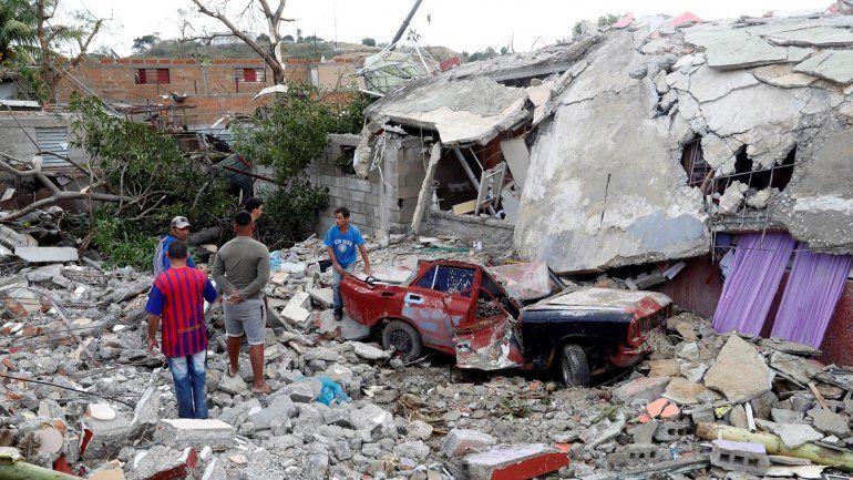 Varias personas miran el estado en que quedó un auto aplastado por los escombros