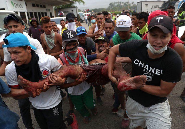 Manifestantes trasladan a un hombre herido durante los enfrentamientos generados ante la negativa de las fuerzas del régimen de dejar pasar la ayuda humanitaria.
