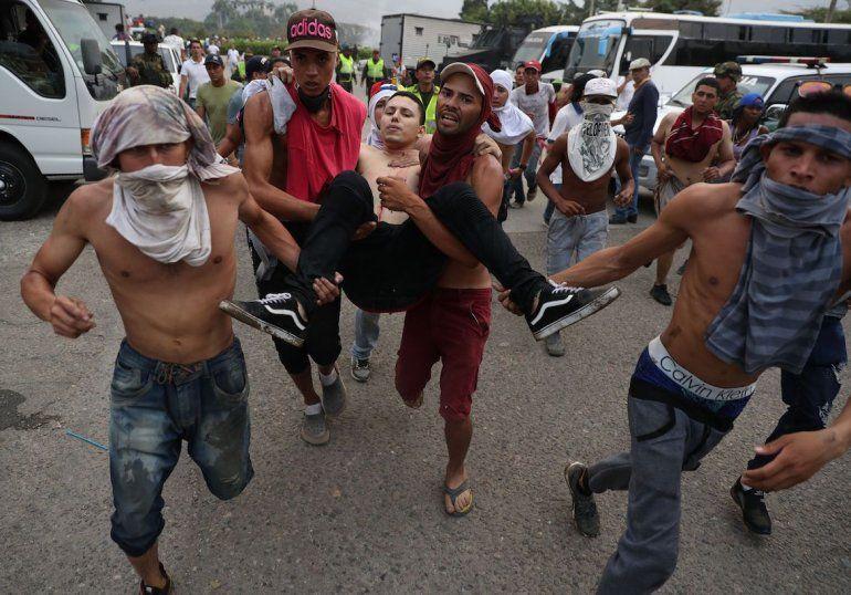 Manifestantes sacan a un joven herido durante las protestas en la frontera colombo venezolana.