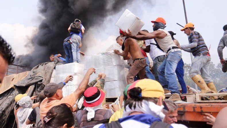 Voluntarios rescatan las cajas con la ayuda humanitaria que fue quemada por grupos irregulares a disposición del régimen de Nicolás Maduro.