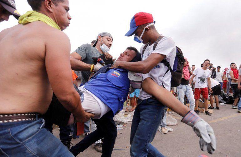 Manifestantes socorren a un hombre herido este sábado en los enfrentamientos entre civiles y militares en la frontera venezolana con Brasil y Colombia