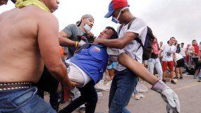 Manifestantes socorren a un hombre herido este sábado en los enfrentamientos entre civiles y militares en la frontera venezolana con Brasil y Colombia, ante la negativa del régimen de Maduro de dejar entrar la ayuda humanitaria.