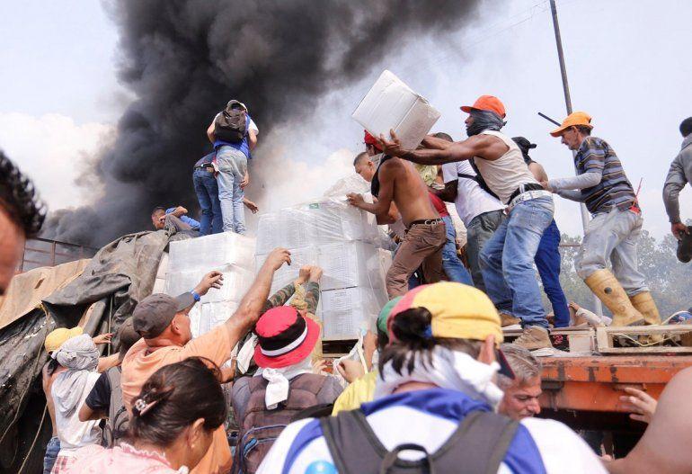 Decenas de personas intentan salvar la ayuda humanitaria de un camión incenciado por efectivos militares del régimen de Nicolás Maduro el 23 de febrero en el lado venezolano del puente Francisco de Paula Santander
