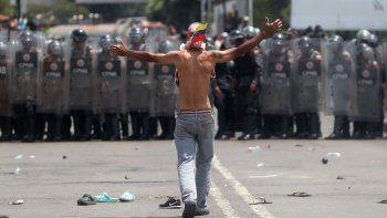 Un opositor venezolano se enfrenta a efectivos de la Guardia Nacional del régimen de Nicolás Maduro que bloqueaban el paso de la ayuda humanitaria por el Puente Internacional Simón Bolívar, en Cúcuta, Colombia.