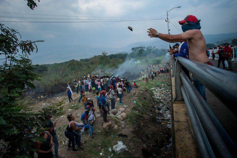 Venezolanos luchan contra una Policía Nacional Bolivariana lanzando piedras.
