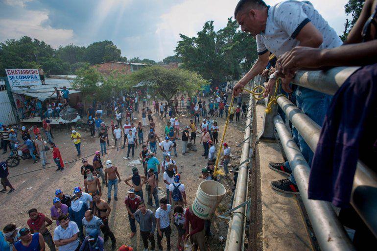 Un hombre sujeta un tono cargado de piedras para entregarlo a los que lanzaban piedras de las fuerzas del régimen.