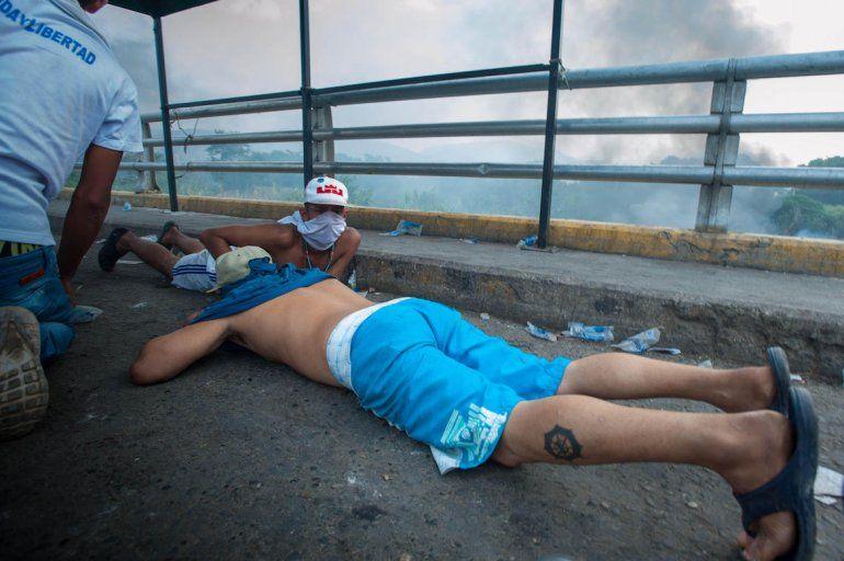 Jóvenes se esconden en el puente ante el ataque de las fuerzas leales al régimen.