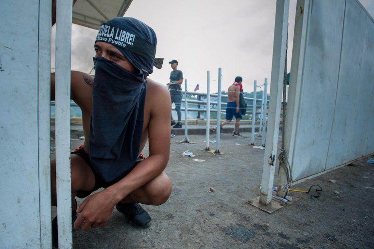 Los venezolanos que intentaron cruzar con la ayuda humanitaria se cubren el rostro para disminuir los efectos de las bombas lacrimógenas.