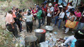 Personas reparten comida en las inmediaciones del puente Francisco de Paula Santander en la frontera entre Venezuela y Cúcuta (Colombia).