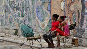Dos mujeres sentadas frente a una pared decorada con graffitis en La Habana, Cuba, en agosto de 2018.