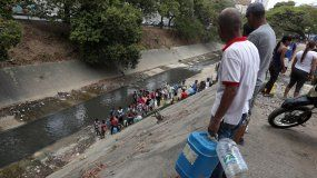 Decenas de personas recogen agua el lunes 11 de marzo en las márgenes del río Guaire, en las inmediaciones de la autopista Francisco Fajardo, en Caracas, Venezuela.