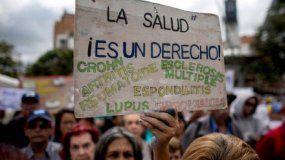 Una mujer muestra un cartel durante una protesta por la escasez de medicinas y tratamientos para la salud en Caracas, Venezuela.