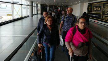 El teniente coronel venezolano Edgar Alejandro Lugo Pereira (2do der.) y sus dos acompañantes, Mildred Josefina Plaza Hernández y Jenny Yamel Rivas González (al frente), son conducidos por un oficial de Migración Colombia en el Aeropuerto Internacional El Dorado, en Bogotá.