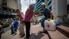 Una señora sale de la sede de la Cruz Roja en Caracas con un kit de agua potable.