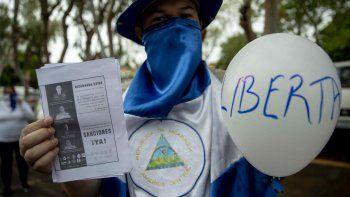 Un hombre con la cara cubierta participa en una protesta este domingo frente a la iglesia San Agustín en Managua (Nicaragua), para exigir al presidente Daniel Ortega la liberación de todos los presos políticos.