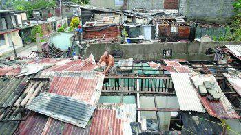 Un hombre trata de colocar láminas de metal para hacer el techo de su vivienda.
