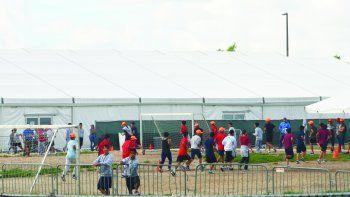 En esta foto tomada desde las afueras del refugio, los niños corren en un campo de fútbol. Al fondo, están las carpas donde se aloja a parte de los menores.