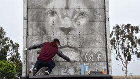 El mexicano Arnulfo González dibuja la figura de un león en la puerta trasera de su camión el 15 de junio, en el estacionamiento del Centro comercial Puente Hills, en City of Industry, California.