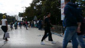 Un grupo de personas camina cerca de la entrada de la heladería Coppelia, en La Habana.