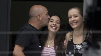 En esta imagen del 20 de septiembre de 2014 se ve a Iván Simonovis, exjefe de la policía de Caracas, mientras le da un beso a su hija Ivana, a un costado de su esposa Bony, mientras se asoman por una ventana en su residencia de Caracas, Venezuela, en donde pasó casi cinco años bajo arresto domiciliario.