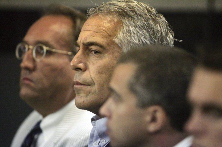 En esta fotografía de archivo del 30 de julio de 2008, Jeffrey Epstein, al centro, es mostrado en custodia en West Palm Beach, Florida.