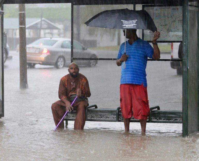 <p>Dos hombres esperan en una parada de autobús en una calle inundada por fuertes lluvias el miércoles 10 de julio de 2019 en Nueva Orleans.</p>