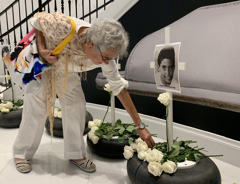 Una mujer pone una flor frente a la fotografía de uno de los niños que murieron tras el crimen del remolcador en 1994.