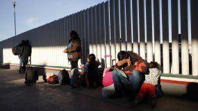 Fotografía de archivo fechada el 25 de enero de 2019 de un grupo de migrantes en la parte mexicana de la frontera a la espera de que les llamen para solicitar asilo en EEUU.
