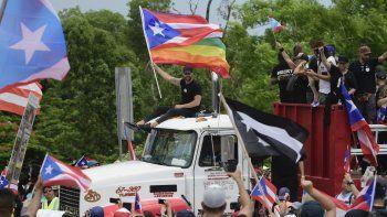 El cantante Ricky Martin, sosteniendo una bandera de Puerto Rico, participa en la marcha en protesta multitudinaria contra el gobierno de Ricardo Rosselló, en San Juan.