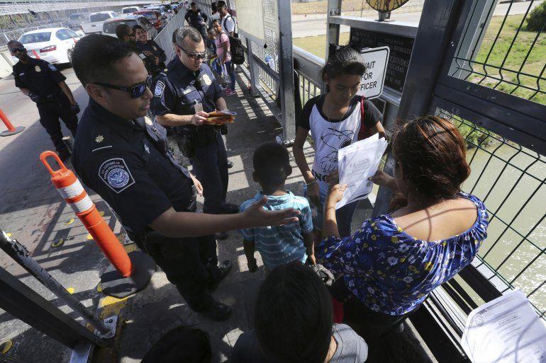 Un agente fronterizo estadounidense verificando los documentos de migrantes antes de ser llevados a solicitar asilo en Estados Unidos