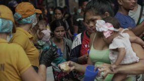 Fotografía de abril de 2019 de un grupo de migrantes venezolanos, la mayoría mujeres, que recibenalimentos en Cúcuta, Colombia.
