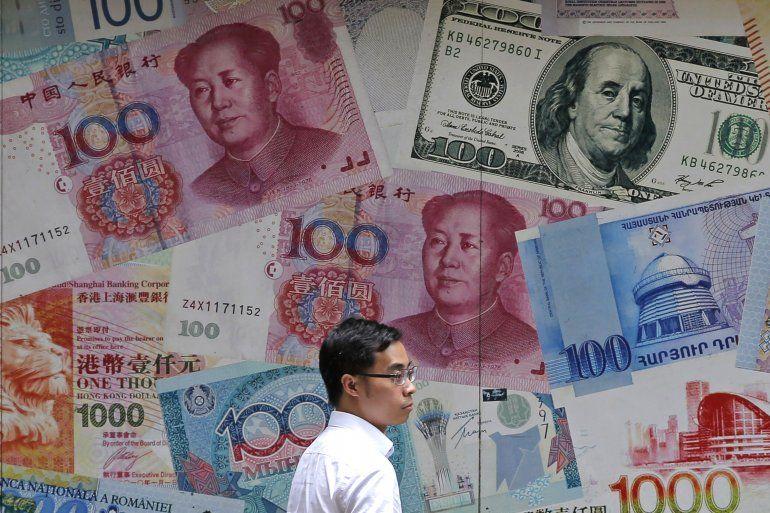 Un hombre camina frente a una casa de cambio, decorada con distintos billetes, en el distrito financiero de Hong Kong. Al menos 180 personas han resultado detenidas a lo largo de las protestas de este domingo en Hong Kong contra la nueva ley de seguridad impuesta desde China.