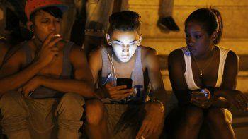 Un grupo de jóvenes consulta la red de Internet en un parque wifi.