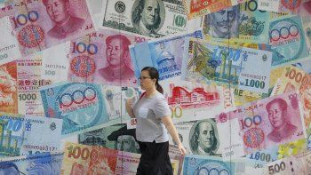 Una mujer camina frente a una casa de cambio en Central, en distrito comercial de Hong Kong.
