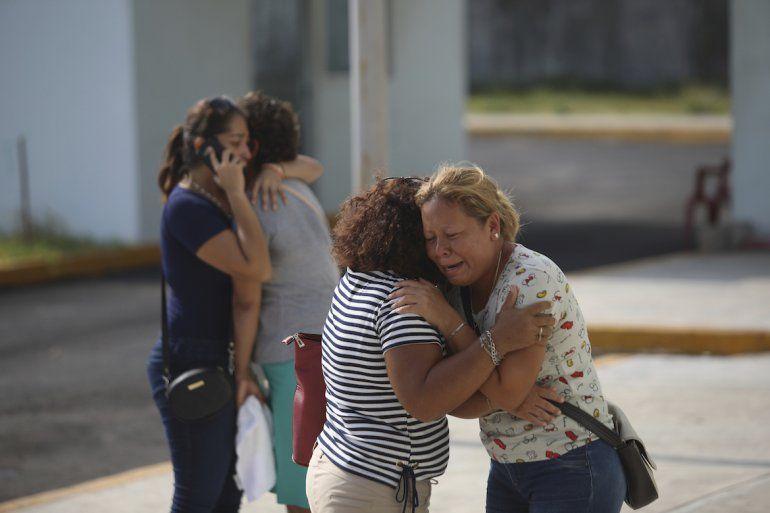 Los familiares de una de las víctimas que murieron durante un ataque a un bar lloran frente a la oficina del fiscal del estado de Veracruz en Coatzacoalcos