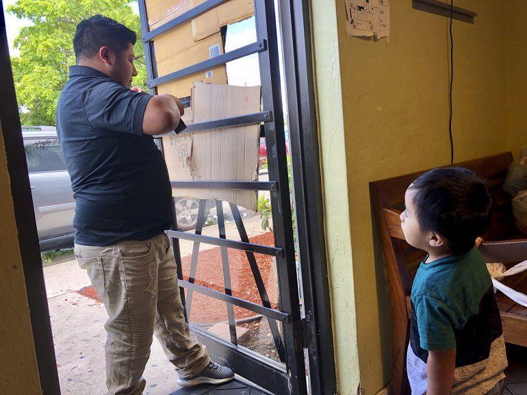 Un hombre protege con cartones la puerta del Guatemalan-Maya Center en Lake Worth, Florida, ante la amenaza del huracán Dorian, el 31 de agosto de 2019.