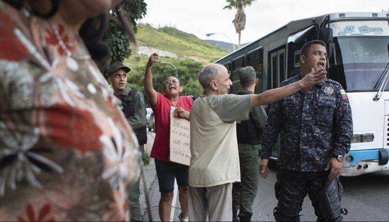 Efectivos de la Guardia Nacional Bolivariana y de la policía del régimen de Nicolás Maduro intentan contener a vecinos que protestan por la falta de agua potable en un barrio de Caracas