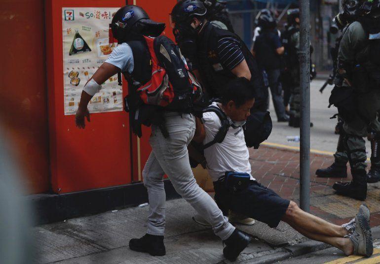 Un manifestante herido es asistido por otros durante un choque con la policía en Hong Kong
