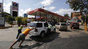 Unas personas empujan un automóvil que se quedó sin combustible en una de las pocas gasolineras que tiene un generador eléctrico durante un apagón en Caracas, el domingo 10 de marzo de 2019.