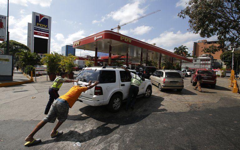 Unas personas empujan un automóvil que se quedó sin combustible en una de las pocas gasolineras que tiene un generador eléctrico durante un apagón en Caracas