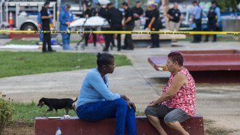 Un par de vecinos habla mientras la policía, al fondo, retira cadáveres de víctimas de una masacre armada en San Juan, Puerto Rico, el martes 15 de octubre del 2019.